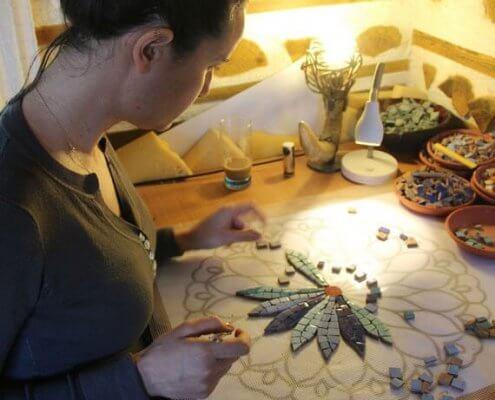 אישה יוצרת תמונת פסיפס אומנותי